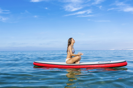 Woman meditating while on a stand up paddle board