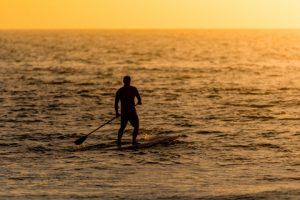 man on stand up paddle board at sunset