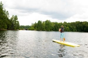 A Young Boy Paddling a SUP on a Lake