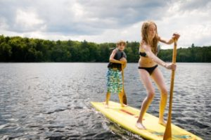 Young boy and girl paddling on a lake