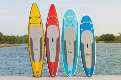 different colored driftsun paddle boards lined up on the shoreline