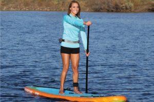 A female paddle boarder paddling on a Sportstuff 1030 iSUP.