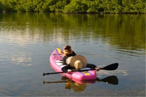 lady and her dog floating on lake on infinito copacabana isup