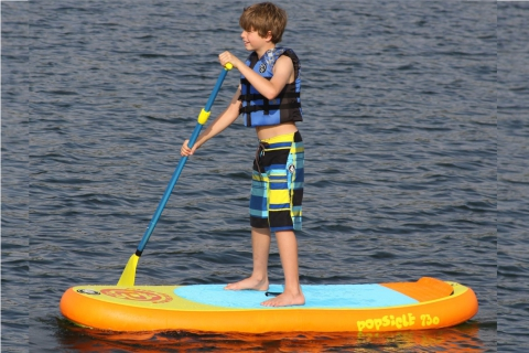 young boy paddling on airhead popsicle isup