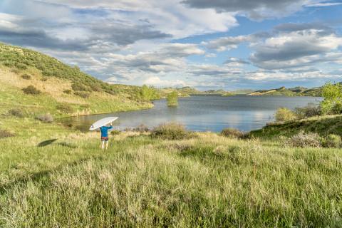 Man carrying SUP board to lake.