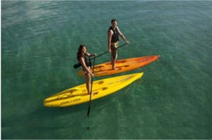 man and woman paddling on ocean kayak nulu paddleboards