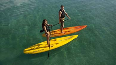 man and woman paddling on ocean kayak nulu paddleboards small