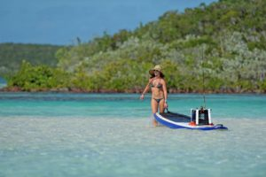 woman-pulling-paddle-board-kayak-with-fishing-gear-out-to-sea